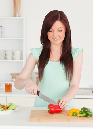 Gorgeous red-haired woman cutting some vegetables in the kitchen in her appartment photo