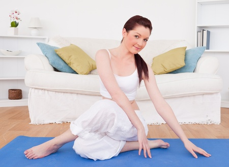 Attractive red-haired female stretching in the living room in her appartment photo