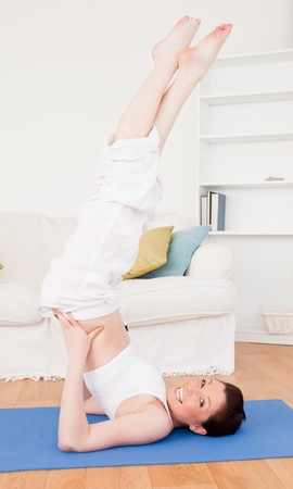 Young good looking red-haired female stretching in the living room in her appartment photo
