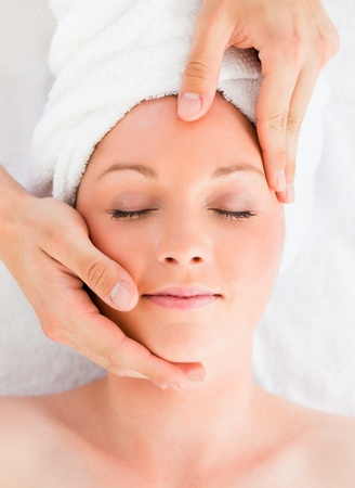 Closeup of a beautiful red-haired woman receiving a massage in a spa centre photo