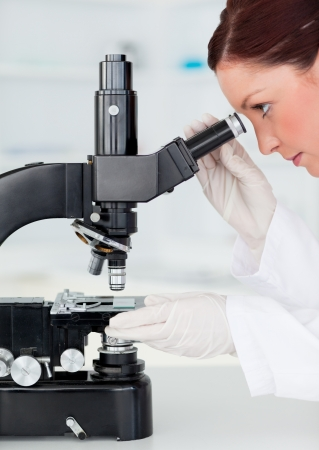 Beautiful red-haired scientist looking through a microscope in a lab photo