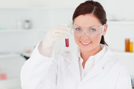 Gorgeous scientist looking at the camera while holding a  test tube in a lab photo