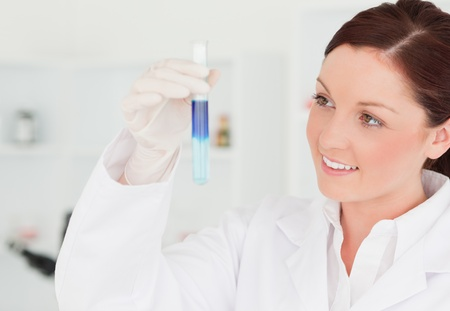 Smiling red-haired scientist looking at a test tube in a lab photo