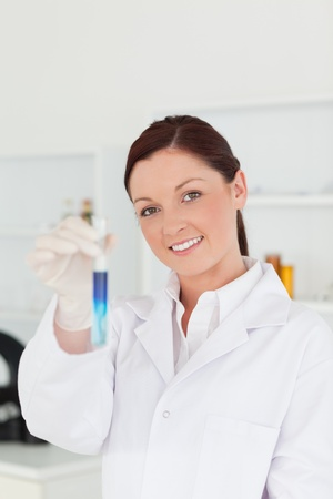Good looking red-haired scientist looking at the camera while holding a test tube in a lab photo