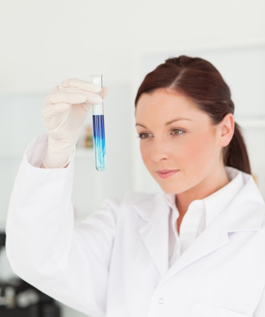 bata de laboratorio: Cient�fico pelirroja hermosa en un tubo de ensayo en el laboratorio