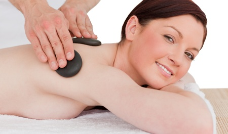 Portrait of a gorgeous red-haired female posing while receiving a massage in a spa centre photo