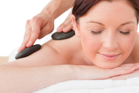 Portrait of a serene red-haired female posing while receiving a massage in a spa centre Stock Photo - 10075995