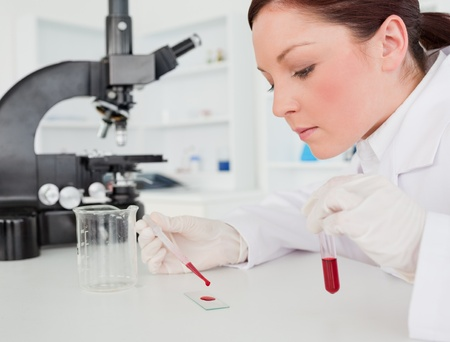 Cute red-haired female scientist doing an experiment in a lab photo