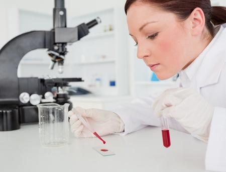 investigador cientifico: Linda pelirroja cient�fica haciendo un experimento en el laboratorio Foto de archivo