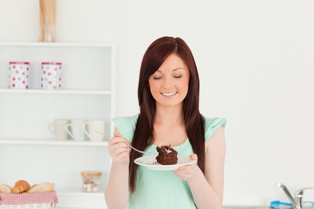 Beautiful red-haired woman eating some cake in the kitchen in her appartment photo