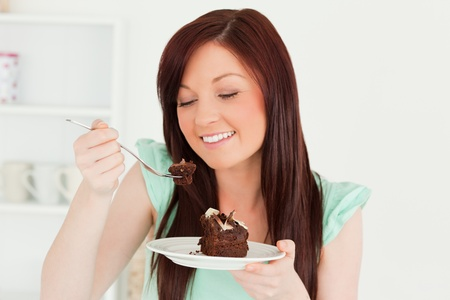 Smiling red-haired woman eating some cake in the kitchen in her appartment photo