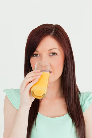 Good looking red-haired woman drinking a glass of orange juice in the kitchen in her appartment Stock Photo - 10069543