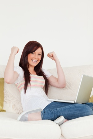 Beautiful red-haired woman being joyful after gambling with her laptop while sitting on a sofa in the living room photo