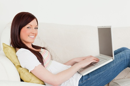Beautiful red-haired woman relaxing with her laptop while lying on a sofa in the living room photo