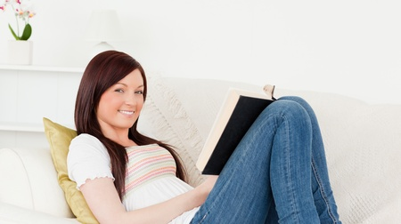 Beautiful red-haired woman reading a book while lying on a sofa in the living room Stock Photo - 10075989