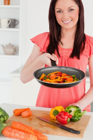 Good looking red-haired woman cooking vegetables in the kitchen in her appartment photo