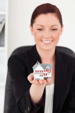 Beautiful red-haired woman in suit holding a miniature house while sitting in an office photo