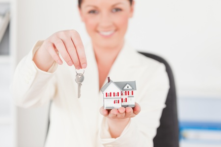 Young gorgeous red-haired female in suit holding a key and a miniature house while sitting in an office photo
