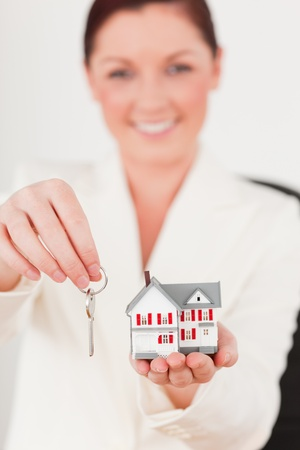 Young attractive red-haired female in suit holding a key and a miniature house while sitting in an office photo