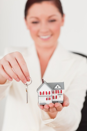Young beautiful red-haired female in suit holding a key and a miniature house while sitting in an office photo