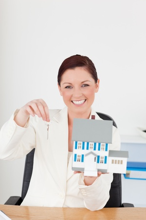 Young pretty red-haired woman in suit holding a blue miniature house while sitting in an office photo