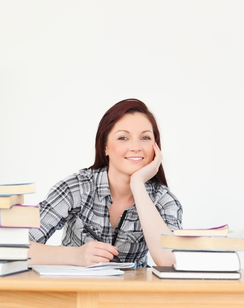 Beautiful joyful red-haired girl studying for an examination at her desk Stock Photo - 10068692