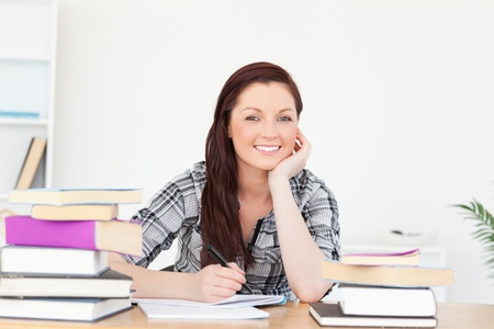 Good looking joyful red-haired girl studying for an examination at her desk Stock Photo - 10069371