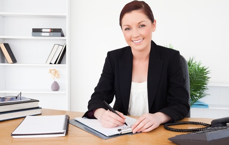 Beautiful red-haired female in suit writing on a notepad and posing while sitting in an office photo