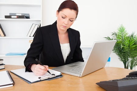 woman with document: Young beautiful red-haired female in suit typing on her laptop and writing on a notepad while sitting in an office