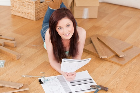 Pretty red-haired girl posing while reading a manual before do-it-yourself at home photo