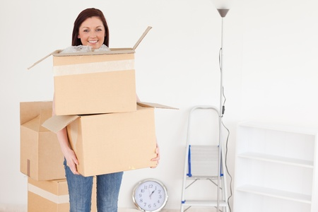 Attractive red-haired woman holding some carboard boxes at home Stock Photo - 10069399