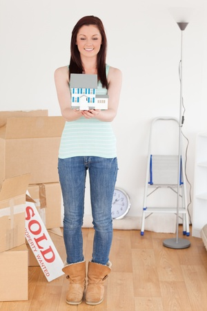 Beautiful red-haired woman holding a miniature house standing on the floor at home photo