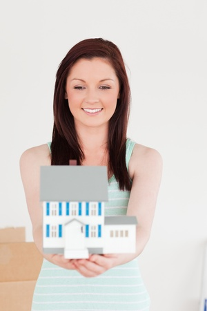 Good looking red-haired woman holding a miniature house while standing on the floor at home photo