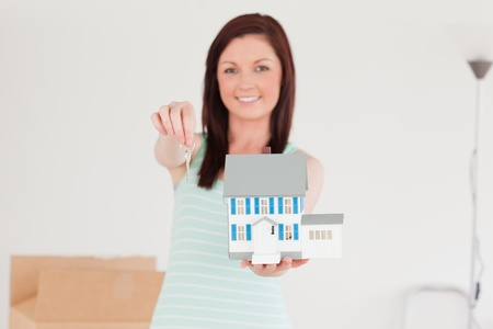 Good looking red-haired female holding a miniature house while standing on the floor at home photo