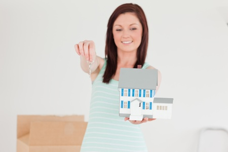 Pretty red-haired female holding a miniature house while standing on the floor at home photo