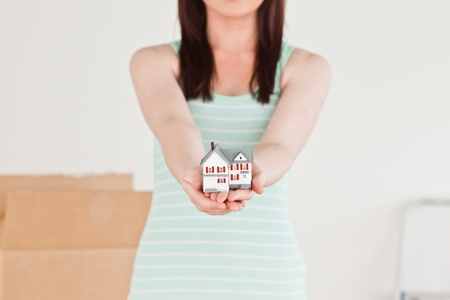 Cute red-haired female holding a miniature house while standing on the floor at home photo