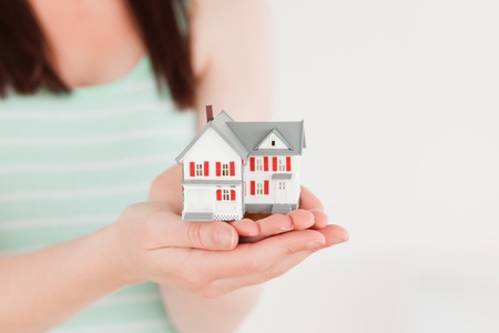 Woman holding a miniature house while standing on a white background photo