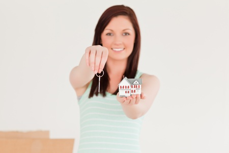 Attractive red-haired female holding a key and a miniature house standing on the floor at home photo