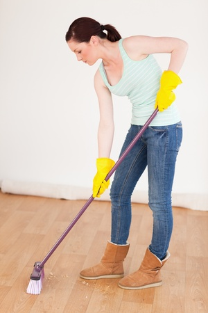 Beautiful red-haired woman sweeping the floor at home photo