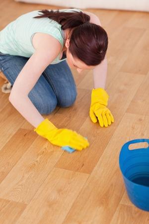 ama de casa: Buena mujer pelirroja busca limpiar el piso mientras arrodillada en casa
