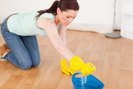 Cute red-haired woman cleaning the floor while kneeling at home photo