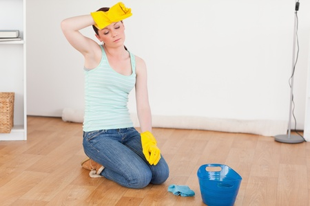Pretty red-haired woman having a break while cleaning the floor at home Stock Photo - 10074192