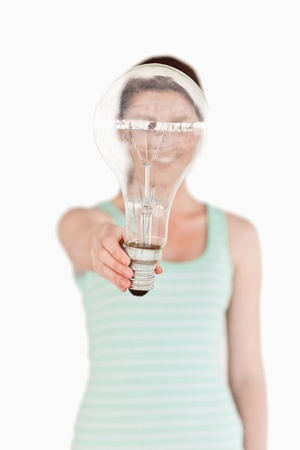 Pretty red-haired female holding a light bulb house while standing on a white background photo