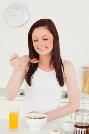 Young attractive red-haired woman having her breakfast in the kitchen in her appartment  photo