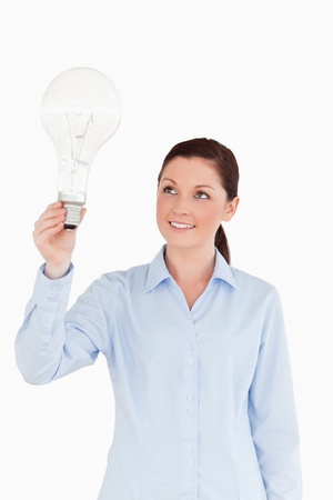 Attractive red-haired female holding a light bulb while standing on a white background photo