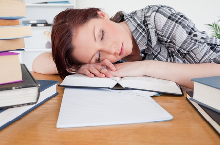 Pretty red-haired girl having a rest while studying at her desk Stock Photo - 10074665