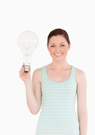 Gorgeous red-haired female holding a bulb while standing on a white background photo