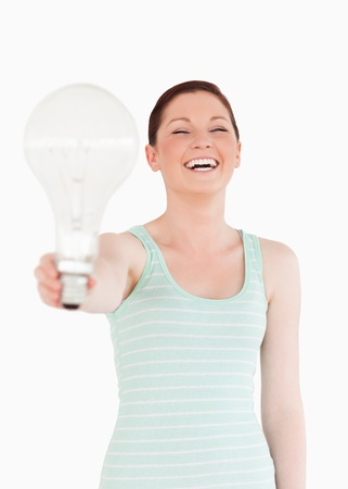 Beautiful red-haired female holding a bulb while standing on a white background photo