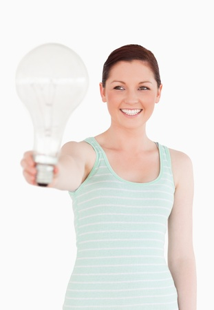 Beautiful red-haired female holding a light bulb while standing on a white background photo