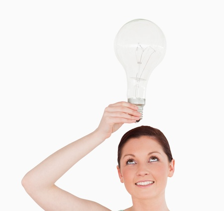 Gorgeous red-haired woman holding a bulb while standing on a white background photo